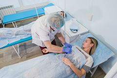Professional nurse making an injection to a woman lying on operating table at the hospital preparing anesthetic medical. Professional nurse making an injection Royalty Free Stock Image