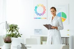 Professional nutritionist in white uniform. In the office with plant and colorful posters Royalty Free Stock Photos