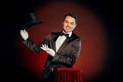 Professional Occupation. Magician in suit and gloves standing isolated on wall making trick showing hat smiling playful royalty free stock photography