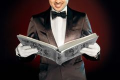 Professional Occupation. Magician in suit and gloves standing isolated on wall reading magic book joyful close-up stock image