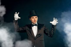 Professional Occupation. Showman in suit gloves and hat standing isolated on wall making mysterious atmosphere. Professional showman wearing suit gloves and top stock photo