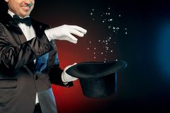 Professional Occupation. Showman in suit and gloves standing on wall making tricks with hat close-up smiling. Professional showman wearing suit and gloves royalty free stock images