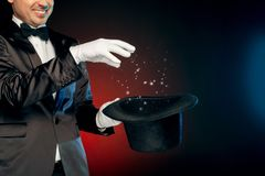 Professional Occupation. Showman in suit and gloves standing isolated on wall making tricks with hat close-up smiling. Professional showman wearing suit and royalty free stock image