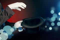 Professional Occupation. Showman in suit and gloves standing on wall making tricks with hat close-up. Professional showman wearing suit and gloves standing on royalty free stock photography