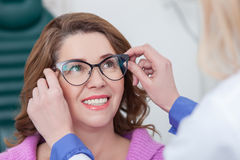 Professional oculist is giving eyewear to the lady Stock Photos