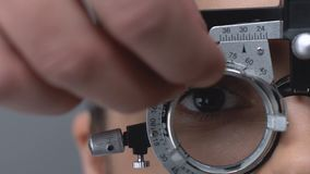 Professional optometrist putting on lens into phoropter to check patient vision stock video footage