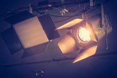 Professional orange studio spotlight in a TV studio. Lighted dust particles. Professional orange studio spotlight hanging on the ceiling. Lighted dust particles stock images
