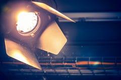 Professional orange studio spotlight in a TV studio. Lighted dust particles. Professional orange studio spotlight hanging on the ceiling. Lighted dust particles stock photos