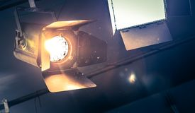 Professional orange studio spotlight in a TV studio. Lighted dust particles. Professional orange studio spotlight hanging on the ceiling. Lighted dust particles stock photo
