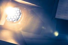 Professional orange studio spotlight in a TV studio. Lighted dust particles. Professional orange studio spotlight hanging on the ceiling. Lighted dust particles stock image
