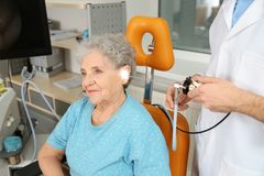 Professional otolaryngologist examining senior woman with endoscope in clinic. Hearing disorder royalty free stock photo
