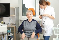 Professional otolaryngologist examining senior woman with endoscope in clinic. Professional otolaryngologist examining senior women with endoscope in clinic royalty free stock photos