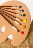 Professional paintbrushes lying on wooden pallet with oil paints Stock Photos