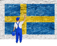 Professional painter covers brick wall with flag of Sweden Stock Photo