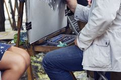 Professional painter doing caricatures. In the street stock photo