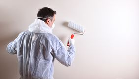 Professional painter with roller on the back of a wall royalty free stock images