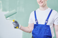 Professional painter with roller. Professional young painter holding a roller and painting a wall Royalty Free Stock Photos