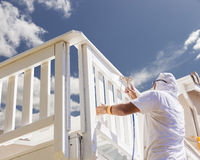 Professional Painter Spray Painting A Deck of A Home. House Painter Wearing Facial Protection Spray Painting A Deck of A Home Royalty Free Stock Images