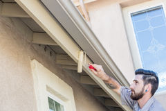 Professional Painter Using Small Roller to Paint House Fascia Stock Photo