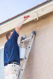 Professional Painter Using Small Roller to Paint House Fascia Royalty Free Stock Image