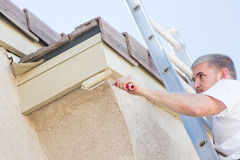 Professional Painter Using Small Roller to Paint House Fascia Royalty Free Stock Images