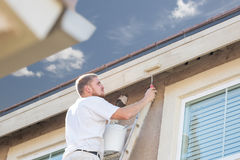 Professional Painter Using Small Roller to Paint House Fascia Stock Image