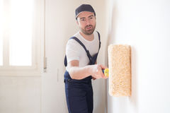 Professional painter worker is painting one wall Stock Photography