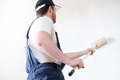 Professional painter worker is painting one wall Royalty Free Stock Photography