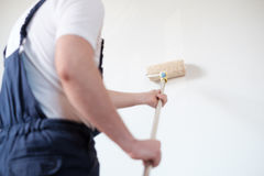 Professional painter worker is painting one wall. Professional painter worker is painting a wall , focus on the roller Royalty Free Stock Photography