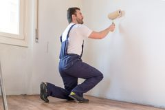 Professional painter worker is painting one wall Stock Photos