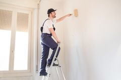Professional painter worker is painting one wall Royalty Free Stock Image