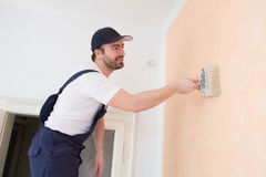 Professional painter worker is painting. A wall Royalty Free Stock Photo