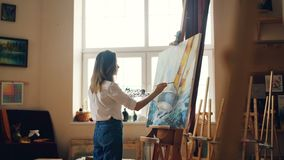Professional painter young lady is painting seascape with acrylic paints depicting marine landscape ship and sea waves stock video