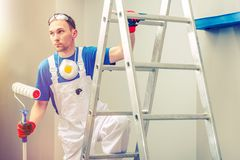 Professional Painting. Professional Painter with Painting Roller on the Ladder royalty free stock photos