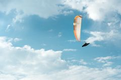 Professional paraglider flies on a white paraglider against the blue sky and white clouds. Paragliding sport royalty free stock photo