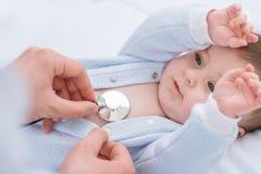 Professional pediatrician examining infant royalty free stock image