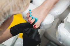 Professional pedicure master making pedicure in salon stock images