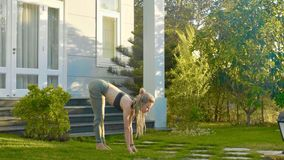 Professional performance of asana yoga by a young girl at backyard of her house stock photo