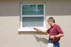 Professional pest control service DIY home owner. A professional pest control service man or do-it-yourself home owner spraying pesticide on the outside of house stock photos