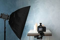 Professional photo equipment and candles on table. Against color wall stock images