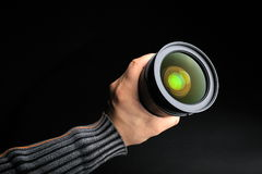 Professional photo lens. In a man´s hand on black background royalty free stock image