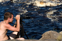 Professional photographer. Working on river bank Stock Images