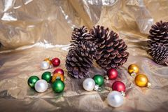 Holiday Christmas scene pine cones and ornaments winter background. Holiday Christmas scene pine cones and multible ornaments winter textured background stock image