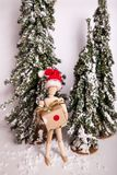 Holiday Christmas wintery scene with wooden jointed doll standing holding gift wearing Santa Claus hat. Holiday Christmas wintery scene with wooden jointed stock image