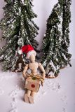 Jointed wooden mannequin doll wearing Santa Claus hat sitting holding a holiday present stock photography