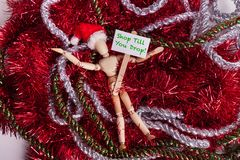 Shop Til You Drop sign held by wooden jointed manikin doll laying on tangled mess of garland wearing Santa hat. Shop Til You Drop sign held by wooden jointed royalty free stock image