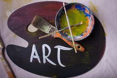 The word ART creatively painted on wooden painters palette dirty paint water and scattered paintbrushes. The word ART creatively painted on wooden painters stock photo