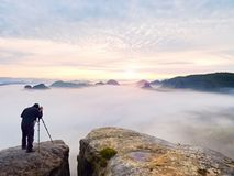 Professional photographer above clouds. Man takes photos with camera on tripod on rocky peak. Professional nature photographer above clouds. Man takes photos Royalty Free Stock Photos