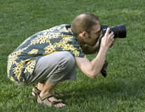 Professional photographer in action outdoors Stock Photos