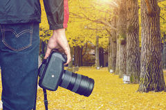 Professional photographer with camera in autumn. Vintage tone Stock Images